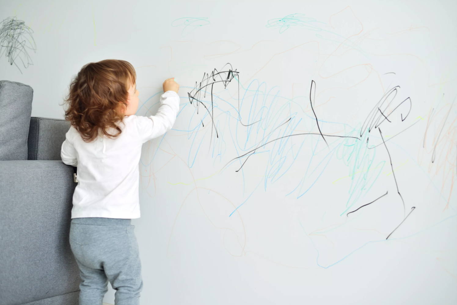 Image of a kid drawing on a wall